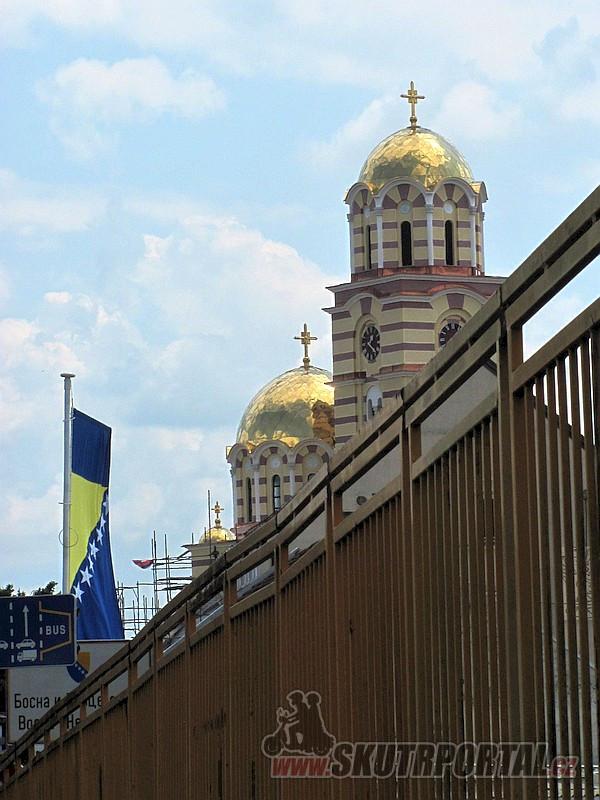 5 Takhle nás vítá Bosna a Hercegovina. Kostely, vlajky, cyrilice… Foceno z auta, v koloně na mostě před celnicí.