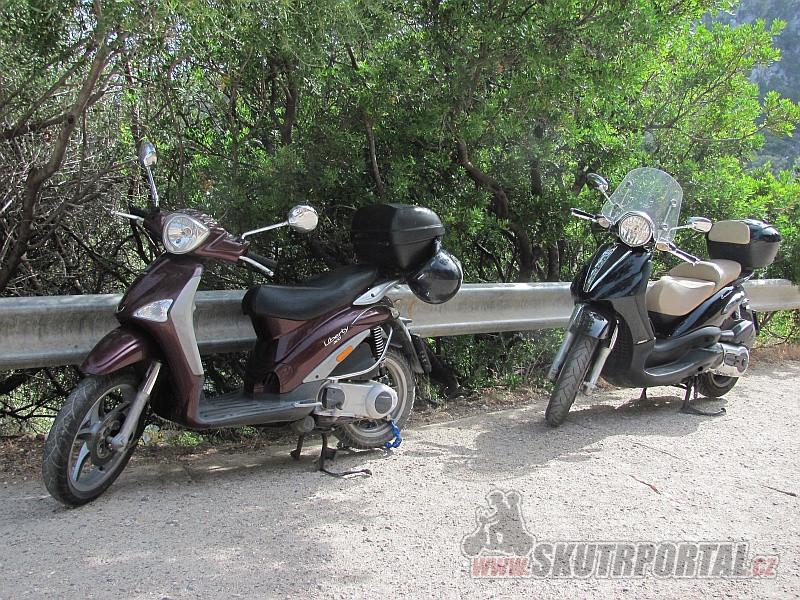 Skútry parkující na silnici nad útesem u pláže Cala Fuili.