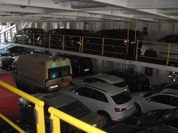02: Vnitřek trajektu se sedmi řadami přepravovaných vozidel, plus po dvou řadách na zavěšených rampách po stranách nákladního prostoru.