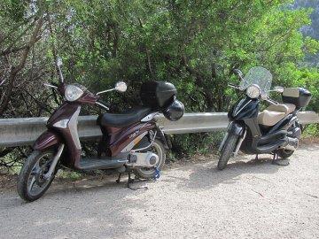 023: Skútry parkující na silnici nad útesem u pláže Cala Fuili.