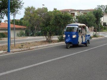 04: Tříkolek jezdí na Sardinii hodně, převažují nákladní. Tahle funguje jako minibus mezi Cala Gonone a pláží Cala Fuili. Slečna řidička byla usměvavá, přátelská, pokérovaná a hulila jako fabrický komín.