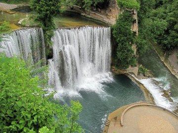 04: 2 Vodopády na řece Pliva v Jajcích a její soutok s Vrbasem. To kulaté je neustále mokrá vyhlídková plošina. Pod vodopády se platí vstupné.