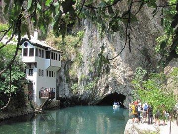 032: 31 Vývěr Buny u Blagaje - řeka vytéká z jeskyně pod vysokou skálou.