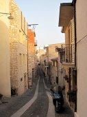 Jedna z úzkých uliček Baunei osvětlená posledními slunečními paprsky dne.