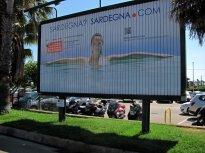 """Parkoviště u letiště v Algheru, naproti vstupu. """"Sardinka"""" z billboardu se s námi loučí a vítá nové návštěvníky."""