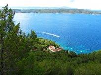 Pohled jižním směrem přes zelené úbočí kopce cestou od tunelu. Vidět je vesnice Zavala, ostrov Ščedro a na horizontu za ním ještě ostrov Korčula.